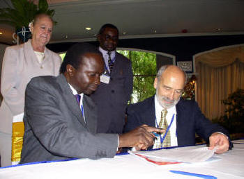 Hon. Daudi Migereko, Minister of Trade, Tourism and Wildlife, Republic of Uganda and Louis D'Amore, IIPT Founder and President sign agreement to on 4th IIPT African Conference to be held in Uganda in partnership with the Africa Travel Association.