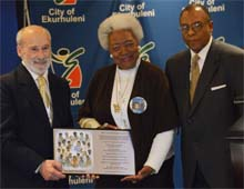 Ms. Naomi King receiving IIPT Plaque from Lou D'Amore and Timothy Marshall